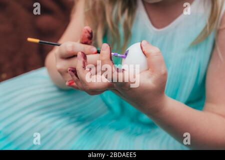 Cute little girl is painting Easter egg with brush, cropped close up photo with targeted focus on the egg.