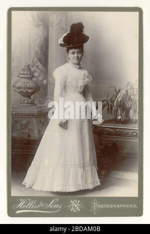 Cabinet card of fashionable, elegant, attractive beautiful Victorian young lady wearing a hat, summer white dress circa 1898, taken in a studio, London, England, U.K.
