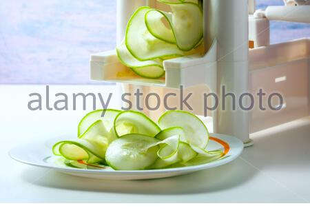 Making zucchini noodles using spiralizer. Selective focus. - Stock Photo