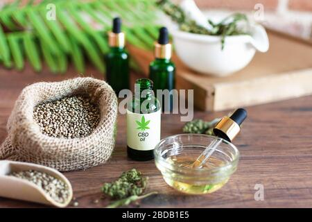 Bottles of hemp oil with cannabis seeds and dry leaves on white wooden table. Medical CBD oil. Alternative medicine concept. - Stock Photo