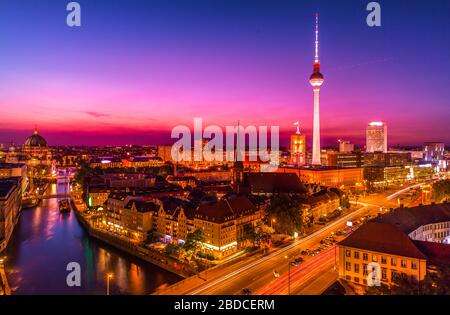 aerial view of Berlin skyline with famous TV tower and Spree river in beautiful post sunset twilight during blue hour at dusk with dramatic sky. - Stock Photo