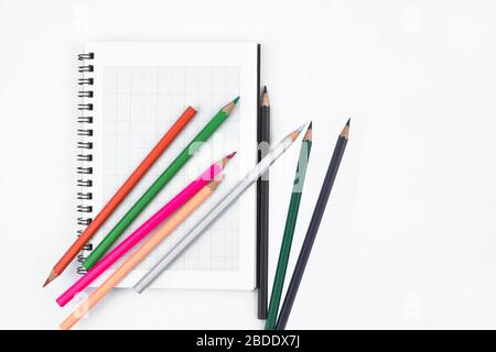 Some different color wood pencil crayons scattered across and on top of a white paper diary - Stock Photo