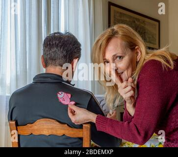 Blonde woman caught in the act while sticking a paper fish for April fools day behind a man, brings her index finger to her mouth to ask for silence