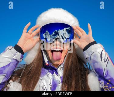 Funny portrait of a young woman in a ski goggles showing tongue on a ski resort. Fun, holidays and active lifestyle concept. - Stock Photo