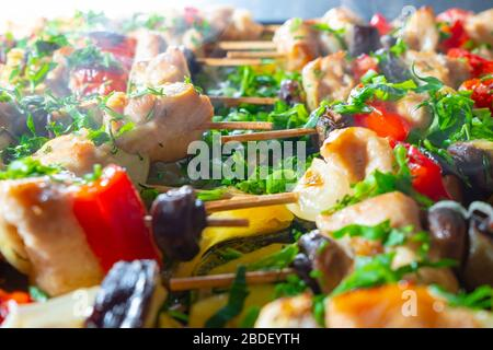 Slices of chicken, eggplant, tomato, sweet peppers and mushrooms are strung on wooden skewers and fried until rosy. Delicious delicacy with freshly ch - Stock Photo