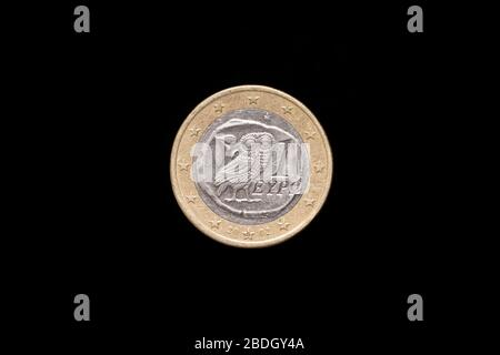 Greek 1 Euro coin from 2002, obverse side showing an owl with an olive branch to the top left. Isolated on black background - Stock Photo