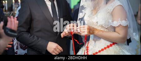 Left hand. Bride is wearing a ring on the hands of a man . Close up shoot of groom's hand putting a wedding ring on the bride's finger. - Stock Photo