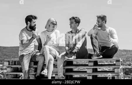 We like spending time together. best friends. Summer vacation. group of four people. great fit for day off. young people talking together. Group of people in casual wear. happy men and girl relax. - Stock Photo