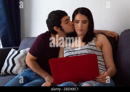 Young adult Hispanic married couple working from home together with a laptop on the sofa at home, kissing each other on the cheek - Stock Photo