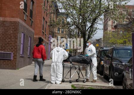 "New York, United States. 07th Apr, 2020. (EDITOR'S NOTE: Image depicts death) Two members of the National Guard retrieve the body of an elderly man who died in his senior citizens apartment building. Mayor de Blasio said that New York City's coronavirus death count is likely to surge as they begin counting those who have died at home.According to the information given by the Governor Andrew Cuomo it would appear that New York state has begun to ""flatten the curve"" with a decrease in hospitalizations and new infections of Coronavirus (Covid-19). Credit: SOPA Images Limited/Alamy Live News - Stock Photo"
