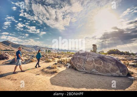 Couple in checkered shirt walking in the open air museum near stone with ancient petroglyph of goats at Kyrgyzstan - Stock Photo