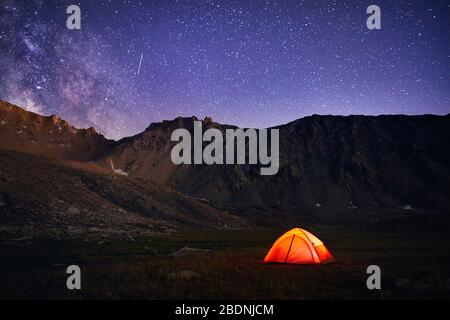 Orange tent glows under night sky full of stars and Milky way in the mountains in Kazakhstan - Stock Photo