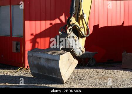 A bucket from the excavator stands on the construction site - Stock Photo
