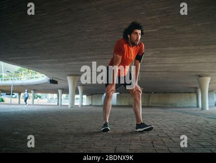 Attractive sporty young man in runner sportswear breathing gasping and taking a break after running workout under the bridge - man running in the new - Stock Photo