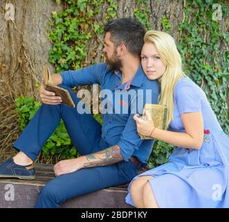 Couple in love hugs outdoor, nature background, defocused. Romantic couple holds old book with poems about love. Girl with pensive face listen bearded man reading poems. Romantic vintage date concept. - Stock Photo