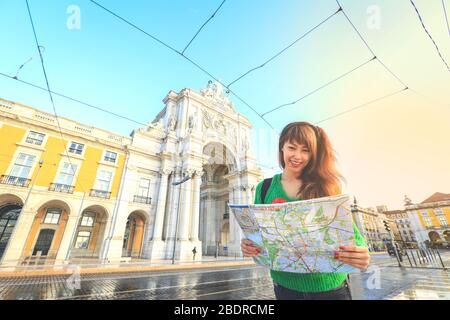 Young asian tourist holding the map and smile while traveling in Lisbon, Portugal - Stock Photo