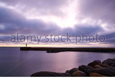Stony breakwater with lighthouse located near tranquil sea water against cloudy sky in evening in countryside - Stock Photo