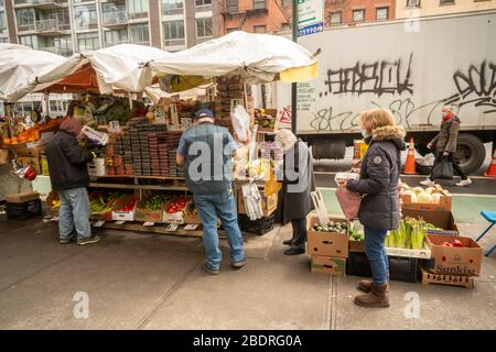 Customers line up at a fruit stand in the Chelsea neighborhood of New York on Saturday, April 4, 2020.  (© Richard B. Levine) - Stock Photo