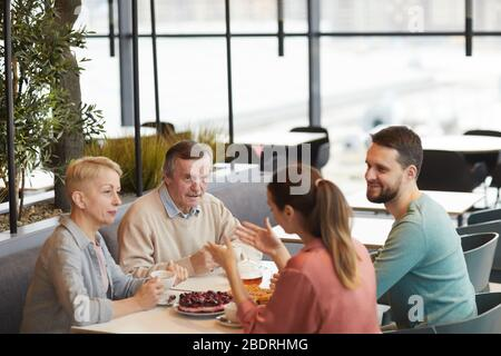 Family of four sitting at the table having breakfast together and talking to each other in cafe - Stock Photo