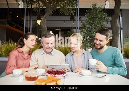 Mature parents with their adult children watching something online on digital tablet while having breakfast at the table at the restaurant - Stock Photo