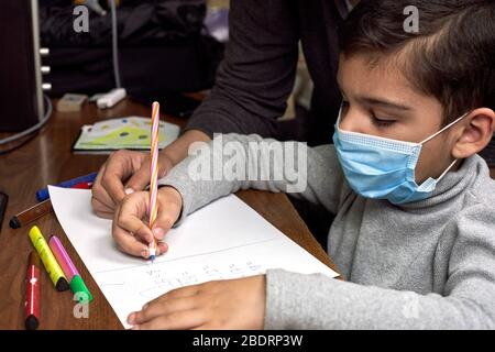 Distance education. Mother helps pre-school kid to do lessons. Education at quarantine time. Protection of Children during the Coronavirus Pandemic