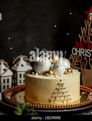 christmas themed cake topped with christmas tree toys in gold and white - Stock Photo