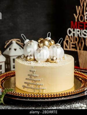 christmas themed cake with christmas tree balls in white and gold - Stock Photo