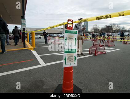 Coronavirus, Cambridge, MA, USA.  08 April 2020.  Customers lineup, queue, in the parking lot outside of Trader Joe's grocery market. - Stock Photo