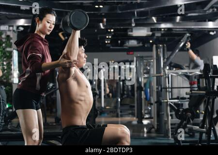 The young man dumbbell with his coach - Stock Photo