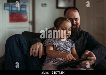 Close up of dad and young daughter playing on tablet during isolation
