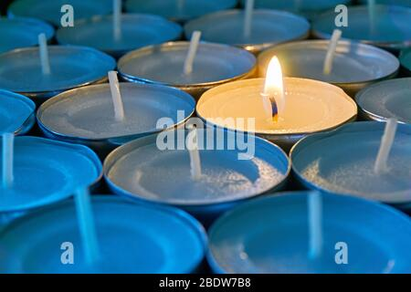 Closeup of tea lights with one being lit. A single warm orange flame between  candles in blue shadow. Christmas, mourning or condolence concept.