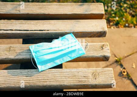 Protective face mask on wooden bench. Typical 3-ply surgical mask to cover the mouth and nose. Procedure mask from bacteria. Protection concept. - Stock Photo