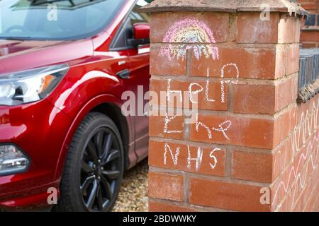Kidderminster, UK. 10th April, 2020. Following a third Thursday evening where the UK nation comes together to Clap For Our Carers, Clap For Our NHS, a new message appears in a UK garden showing how children too are expressing their understanding and appreciation. A colourful rainbow and simple chalk message, Help The NHS, are lovingly drawn on a front garden wall for pedestrians to see as they pass in the street for their daily exercise. Credit: Lee Hudson/Alamy Live News