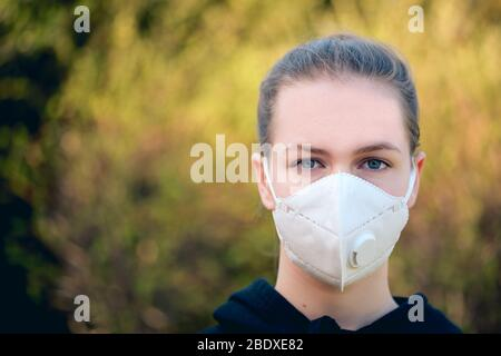 young girl with anti-virus anti-smog mask on her face. Wearing hygiene masks reduces the risk of getting COVID-19 disease caused by coronavirus; it al - Stock Photo