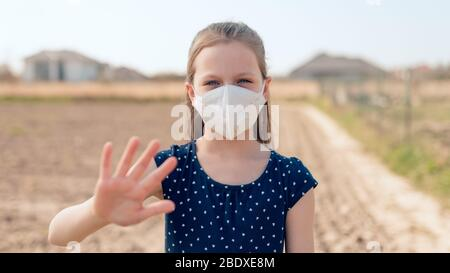 Coronavirus and air pollution concept. Little Caucasian girl wearing face mask for protection and showing stop hand gesture for stoping corona virus o - Stock Photo