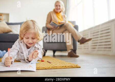Little boy with blond hair lying on the floor and drawing with colored pencils with his grandmother reading a book in the background - Stock Photo