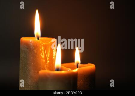 Group of three brown burning candles on a black background close-up. Concept of comfort,romance,mystic,occultism,religion,a symbol of memory.Copy