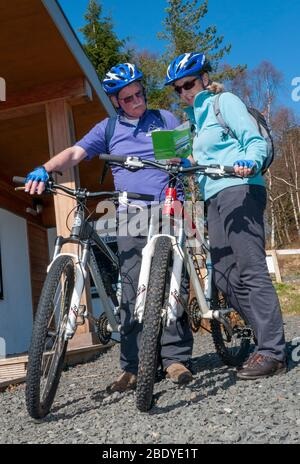 Cyclists on mountain bikes and wearing helmets choosing a cycle route in Kielder Water & Forest Park. Northumberland, North of England, UK - Stock Photo
