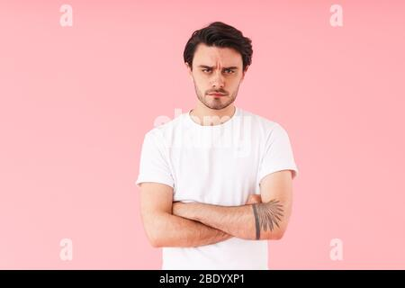 Image of caucasian perplexed man with bristle looking at camera with hands crossed isolated over pink background
