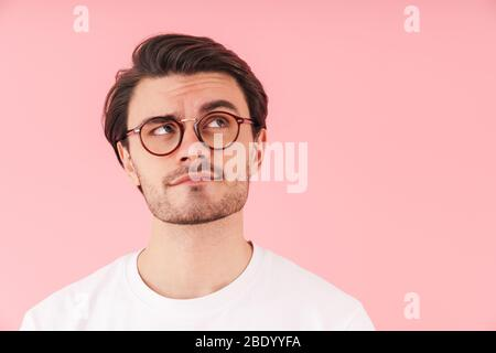 Image of thinking caucasian man wearing eyeglasses looking upward at copyspace isolated over pink background