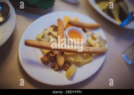 Cheese platter on a white plate with bread sticks and honey. - Stock Photo
