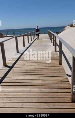 Woman at wooden boardwalk at the beach at Costa Nova do Prado  Ilhavo (Ílhavo) near Aveiro Portugal. - Stock Photo