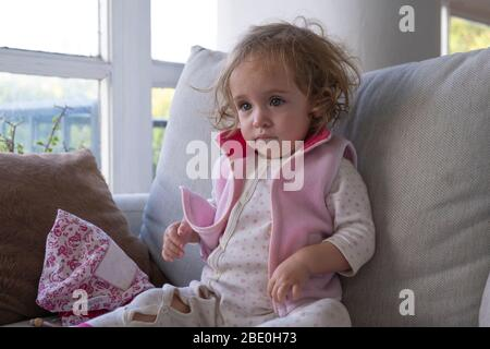 Little girl concentrate watching tv alone in her living room.