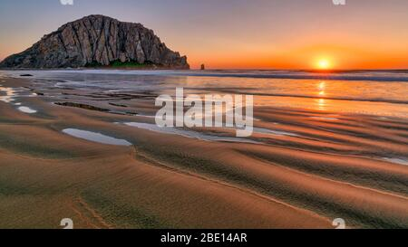 Sunset over the sandy beach of Morro Rock - Stock Photo