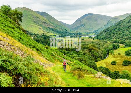 Mountain biker climbing towards Boredale Hause in the Lake District. Brothers Water, Caudale Moor, Kirkstone Pass and Red Screes behind.
