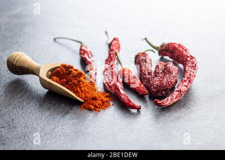 Dried red chili peppers and chili powder spice in wooden scoop. - Stock Photo