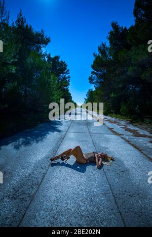 Teenage girl aka young woman lying on lonely concrete road - Stock Photo