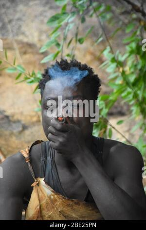 Hadza man smoking from a traditional clay pipe Photographed near Lake Eyasi, Tanzania, Africa Stock Photo