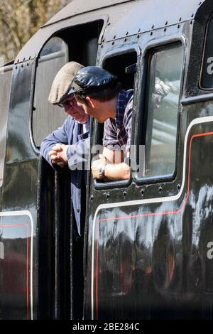 Driver and fireman looking out of the cab window of their Class 4MT steam loco - Stock Photo