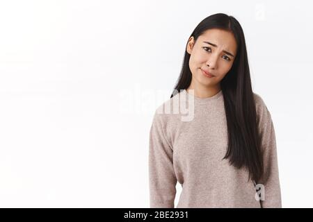 Skeptical, doubtful and displeased young east-asian girl smirk and tilt head, frowning look pity and upset, dont like results, feeling disappointed